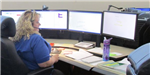 Woman sitting at 911 communications desk with four screens