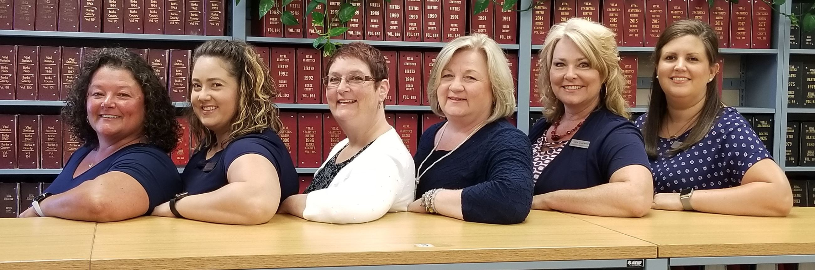 Register of Deeds Staff standing behind a bookcase